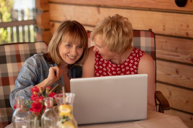 Twee oudere vrouwen hebben zich geregistreerd op een datingsite en overwegen de kandidaten die ze leuk vinden
