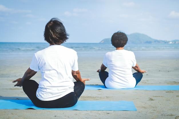 Twee oudere vrouwen zitten op het zand, doen yoga aan zee