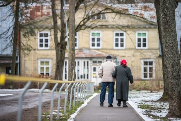 Twee ouderen - man en vrouw lopen langs de weg tegen gebouw. ongelukkige oude dag.