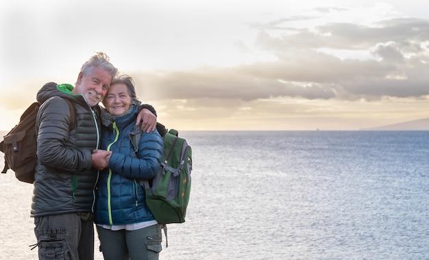 Twee ouderen omhelzen elkaar voor de zee en genieten van het zonsonderganglicht staande op de klif