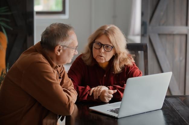 Twee ouderen surfen op internet op laptopcomputer thuis. 4k-video