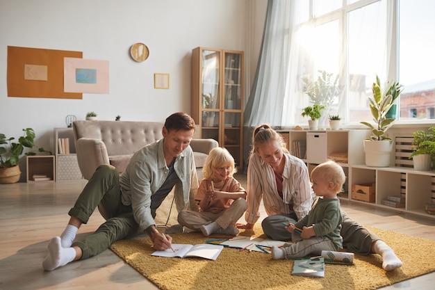 Twee ouders tekenen op de grond samen met hun twee kinderen in de woonkamer