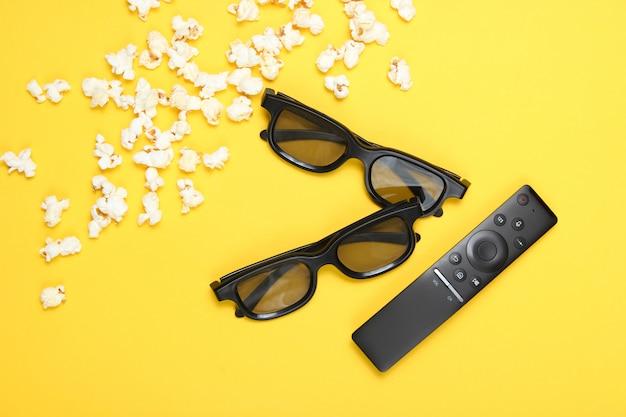 Twee paar 3d-bril, tv-afstandsbediening, popcorn op geel. bovenaanzicht, plat lag