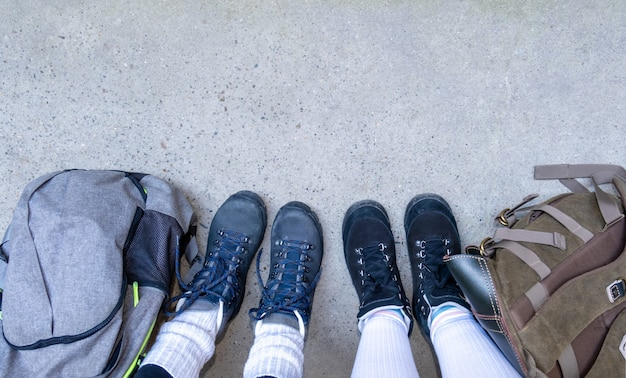 Twee paar benen in laarzen om te wandelen staan op de grijze stoep met rugzakken.