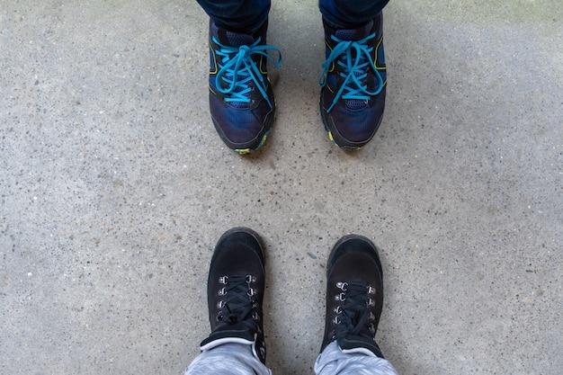 Twee paar benen in laarzen om te wandelen staan op de grijze stoep.