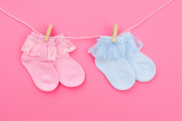 Twee paar blauwe en roze schattige babysokken die aan de waslijn op roze achtergrond hangen. accessoires voor baby's. plat leggen.