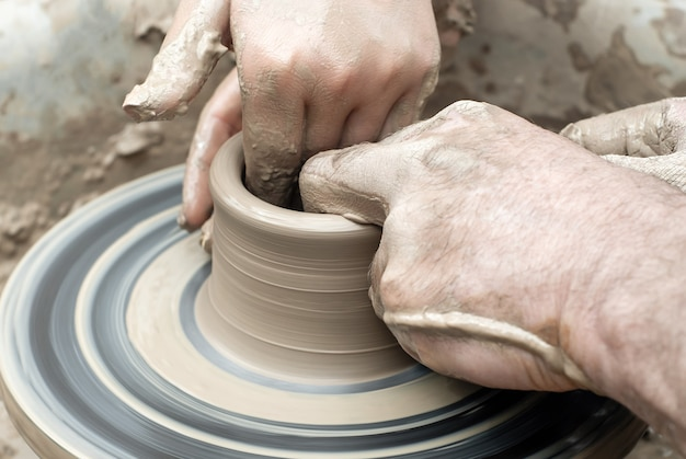 Twee paar handen man en vrouw vormen iets van klei op een pottenbakkersschijf