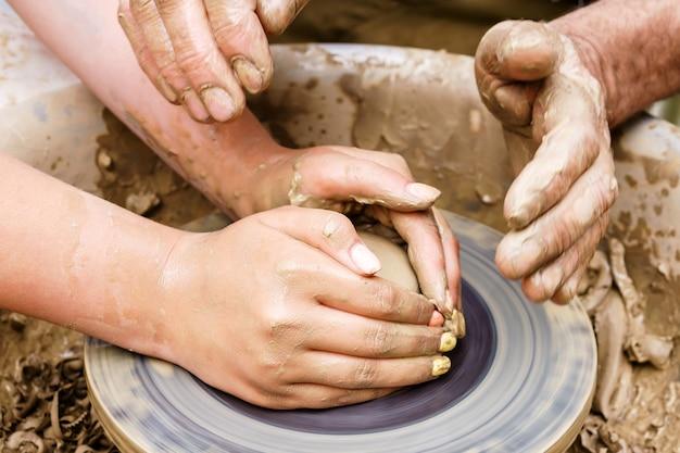 Twee paar handen mannelijk en vrouwelijk of jong en oud vormstuk van klei op een pottenbakkersschijf
