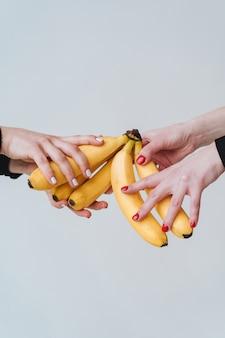 Twee paar handen met een paar bananen