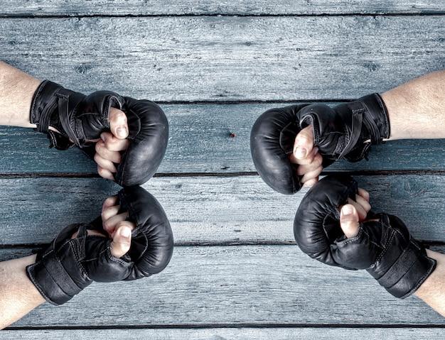 Twee paar menselijke handen in zwart lederen bokshandschoenen tegenover elkaar