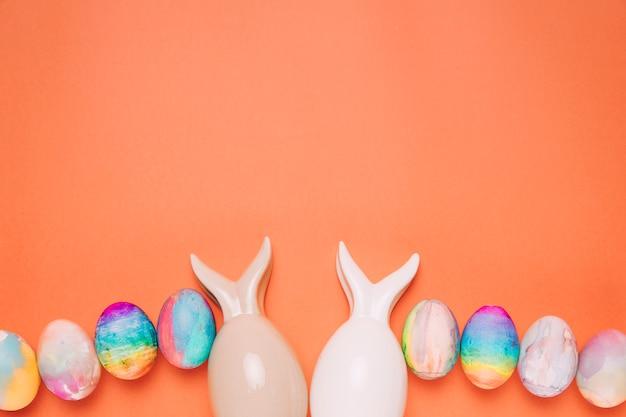 Twee paaseieren met konijntjesoor op oranje achtergrond