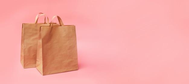 Twee papieren ambachtelijke pakketten, op een roze achtergrond, banner, kopie ruimte, mock-up