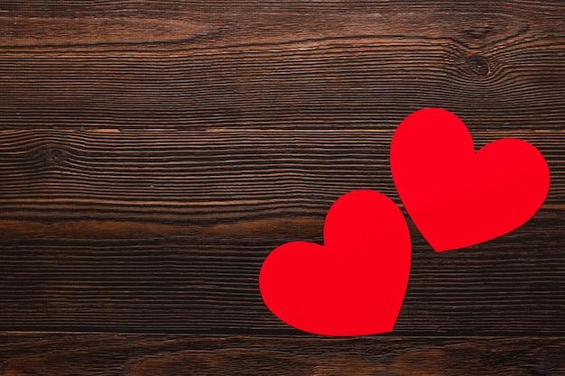 Twee papieren harten geïsoleerd op een donkere houten achtergrond. bovenaanzicht van een feestende warme flatlay. valentijnsdag en kerst concept. copyspace.