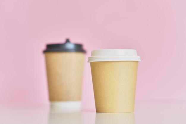 Twee papieren koffiekoppen op roze achtergrond. creatieve mockup-afbeelding