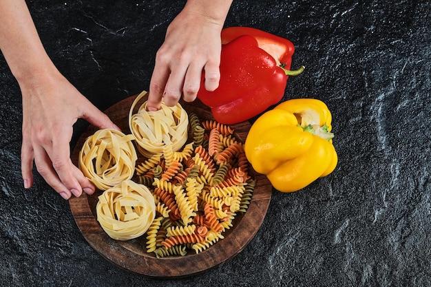 Twee paprika's met rauwe pasta en ongekookte macaroni op zwart.