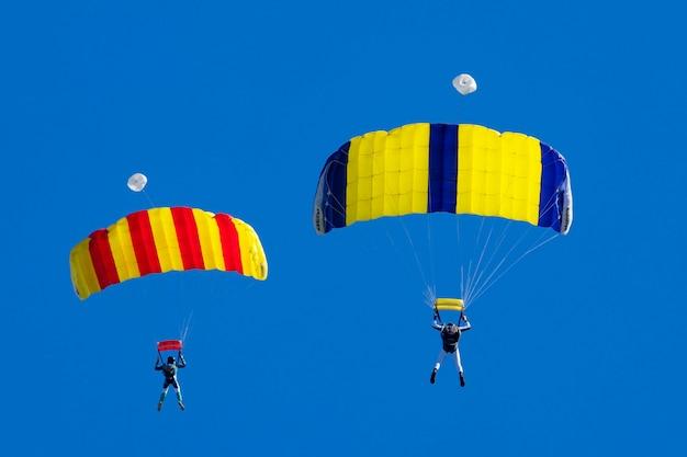 Twee parachutisten tegen een blauwe lucht