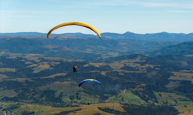 Twee paragliders die boven groene bergen vliegen
