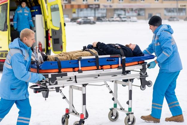 Twee paramedici in blauwe werkkleding duwen brancard met zieke bewusteloze man om hem in ambulanceauto te krijgen en naar het ziekenhuis te brengen
