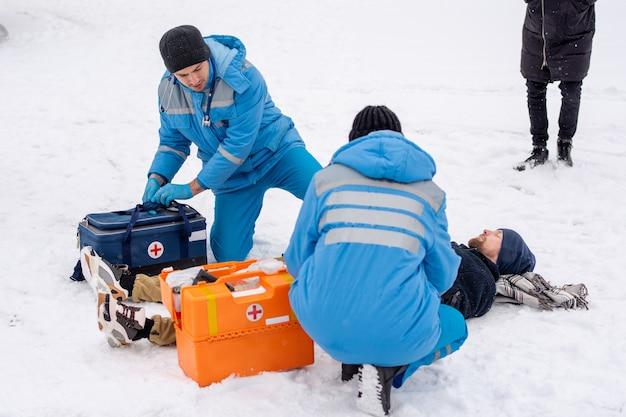 Twee paramedici in uniform bukken zieke bewusteloze man liggend op sneeuw terwijl hij hem eerste hulp buitenshuis