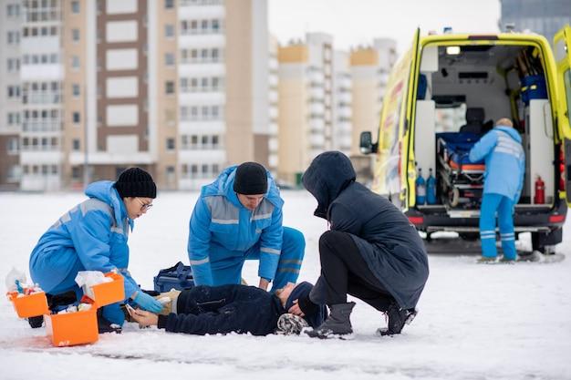 Twee paramedici in uniform en man bukken zieke bewusteloze man liggend op sneeuw terwijl hem eerste hulp buitenshuis