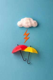 Twee paraplu's onder de wolk op hemelsblauwe achtergrond