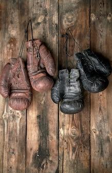 Twee paren leer uitstekende bokshandschoenen die op spijker hangen