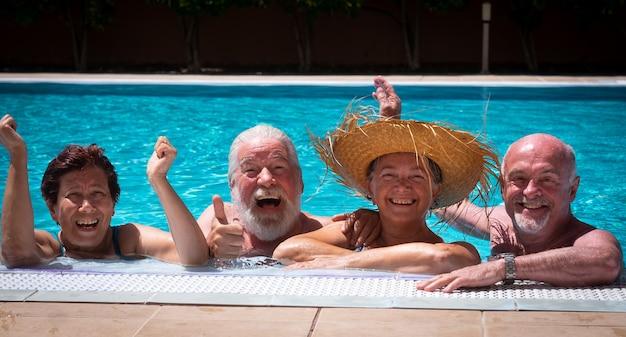 Twee paren van senior mensen vrienden lachen samen genieten van het zwembad. fel zonlicht en transparant water. grote glimlach en geluk
