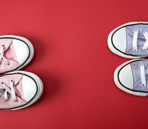 Twee paren versleten klassieke textielparen schoenen op een rode achtergrond