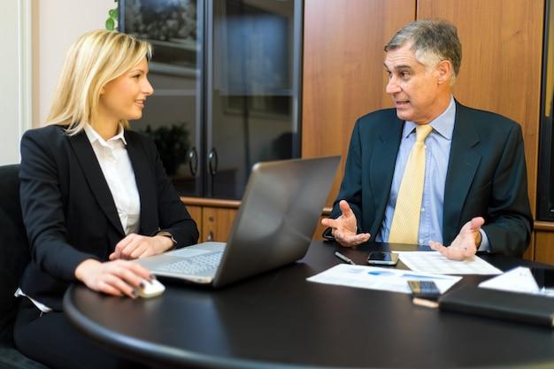 Twee partners die plannen of ideeën bespreken op vergadering