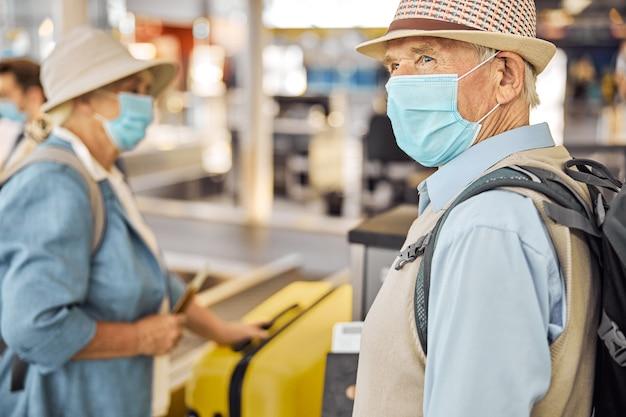 Twee passagiers met beschermende maskers die hun bagage op de transportband op de luchthaven plaatsen