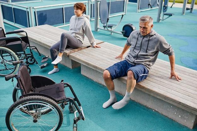 Twee patiënten die buiten op de bank zitten, rusten uit na sportoefeningen die ze herstellen met ...