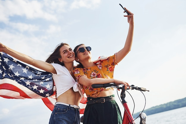 Twee patriottische vrolijke vrouwen met fiets en usa-vlag in handen maken selfie.