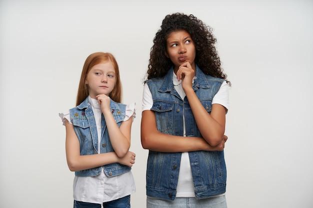 Twee peinzende jonge dames in jeansvesten en witte overhemden die bedachtzaam in verschillende kanten kijken en hun kin vasthouden met opgeheven handen, staande tegen wit