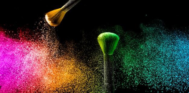 Twee penselen met pastel make-up poeder om een kleurrijke wolk te maken.