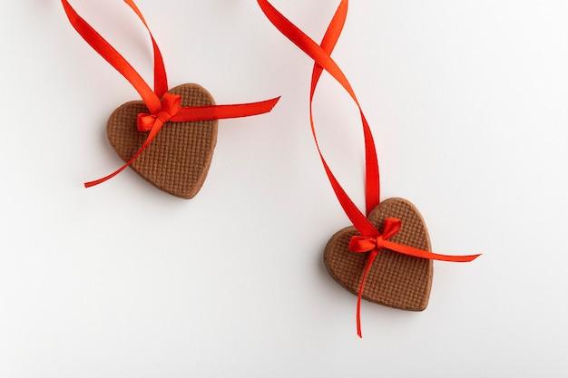 Twee peperkoek harten op valentijnsdag met rood lint op witte achtergrond. detailopname.