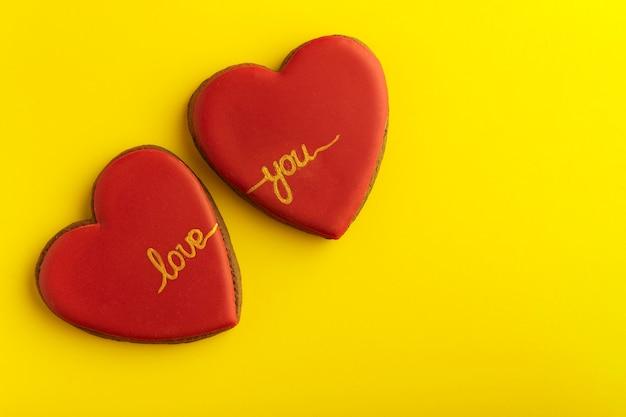 Twee peperkoekkoekjes in de vorm van harten met rood glazuur en inscriptie love you op gele achtergrond.