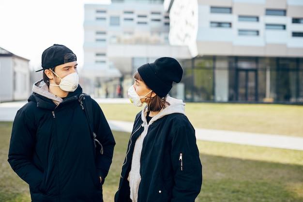 Twee personen lopen op straat in ademhalingsmasker terwijl coronavirus met moderne architectuur aan de muur, paar praten in gezichten bedekt door maskers