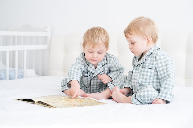 Twee peuterbaby tweelingjongens in pyjama's lezen boek zittend op wit beddengoed op bed