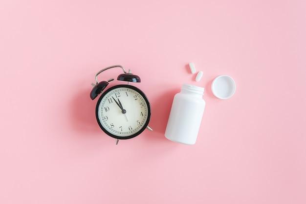 Twee pillen, witte fles en zwarte wekker concept slapeloosheid, slaapproblemen, tijd om pillen te nemen