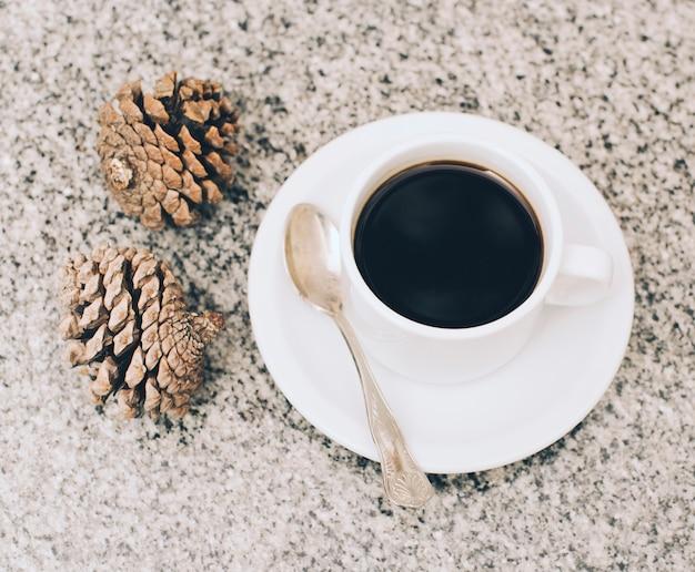 Twee pinecones en kopje koffie op gestructureerde achtergrond