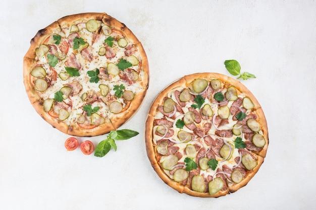 Twee pizza's met verschillende vullingen met caesarsaus, varkensvlees, spek, augurken, worst, tomaten en mozzarella-kaas op een lichte achtergrond. bovenaanzicht met een kopie ruimte voor de tekst. klassiek italiaans eten