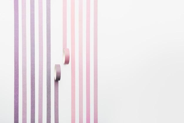 Twee plakbandrollen en parallelle stroken op witte achtergrond