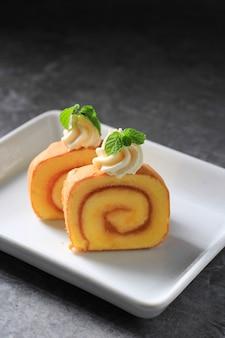 Twee plakjes ananasbroodjescake of bolu gulung nanas, dunne cake gerold met ananasjam met kaasglazuur erop.