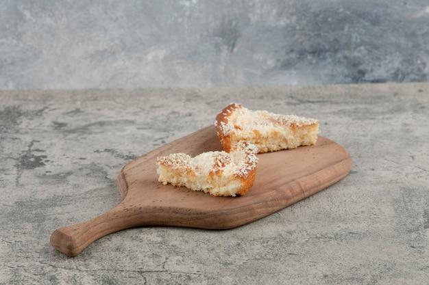 Twee plakjes cake met kokos hagelslag op een houten bord.