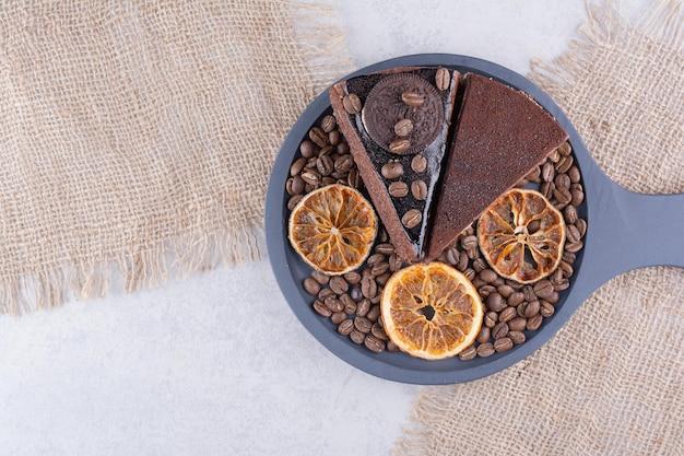 Twee plakjes chocoladecake met koffiebonen en stukjes sinaasappel.