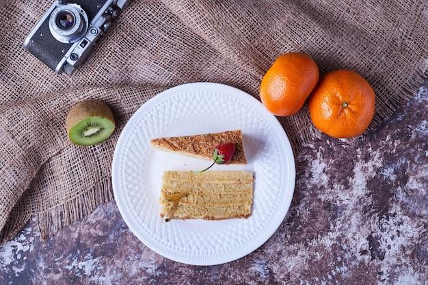 Twee plakjes medovic cake met fruit.