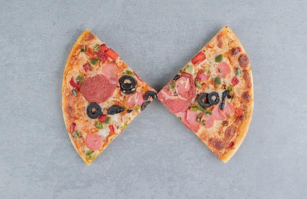 Twee plakjes pizza weergegeven op marmer