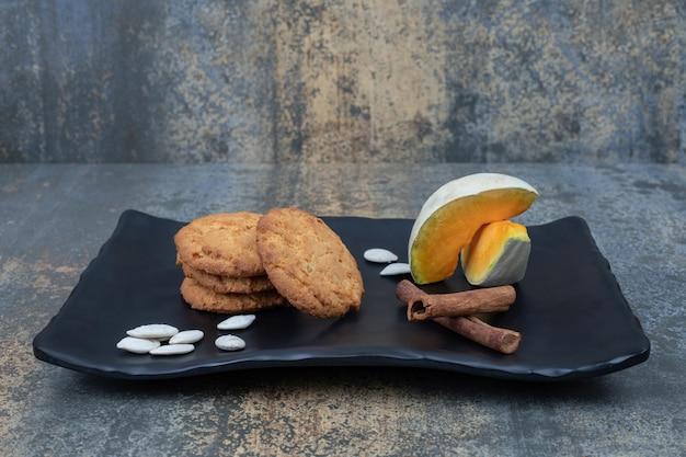 Twee plakjes pompoen met koekjes en kaneel op donkere plaat.