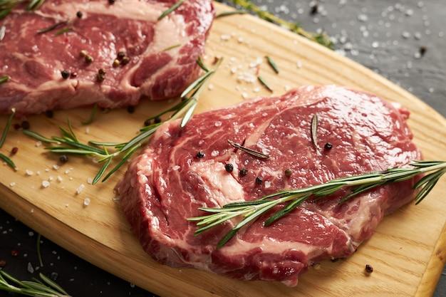 Twee plakjes rauw rundvlees voor barbecue op een houten bord