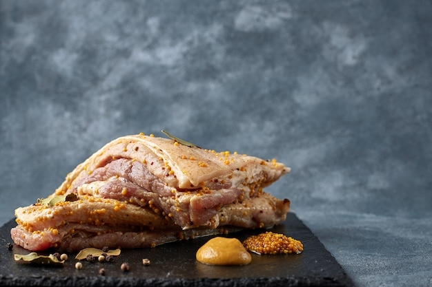 Twee plakjes rauwe reuzel met een laagje vlees, met mosterd, peper en laurier